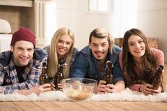 Jeunes amis se trouvant sur le tapis avec des bouteilles à bière et souriant à l'appareil-photo Photos libres de droits