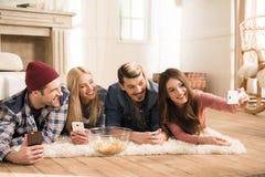 Jeunes amis se trouvant sur le tapis et prenant le selfie à la maison Image stock