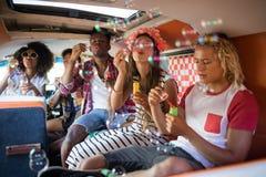 Jeunes amis soufflant des baguettes magiques de bulle dans le camping-car Images stock