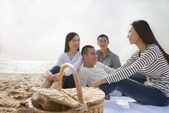 Jeunes amis souriant et riant et ayant un pique-nique sur la plage Images stock