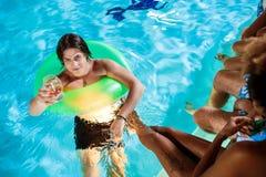 Jeunes amis souriant, se réjouissant, se reposant à la partie près de la piscine Photographie stock libre de droits