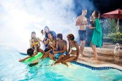 Jeunes amis souriant, se réjouissant, se reposant à la partie près de la piscine Photographie stock