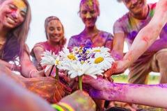 Jeunes amis tenant des camomilles au festival de holi Photos libres de droits