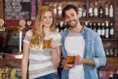 Jeunes amis tenant la bière au bar Images stock