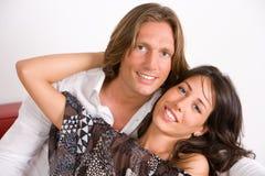 Jeunes amoureux embrassés sur le sofa Images stock