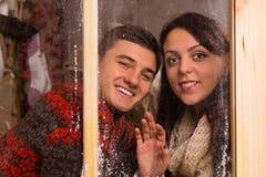 Jeunes amoureux souriant derrière le vitrail Photos stock