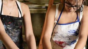 Jeunes artistes attirants travaillant dans le studio d'art banque de vidéos