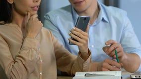 Jeunes associés analysant le revenu et prévoyant le budget de société utilisant l'appli mobile clips vidéos