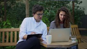Jeunes associés discutant leur projet sur le banc de parc en été banque de vidéos