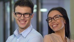 Jeunes associés pleins d'assurance regardant aux meilleurs services de caméra sur le marché clips vidéos