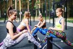Jeunes athlètes féminins s'étirant avant le fonctionnement en parc Images libres de droits