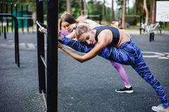 Jeunes athlètes féminins s'étirant avant le fonctionnement en parc Photo libre de droits