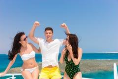 Jeunes attirants ayant l'amusement et la position sur le yacht à Photographie stock libre de droits