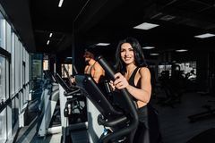 Jeunes attirants de femme de forme physique de brune établissant sur un entraîneur elliptique dans le gymnase Image libre de droits