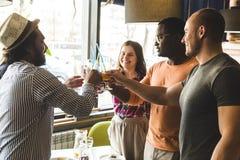Jeunes attirants de rassemblement dans le caf? Les amis causent, ont l'amusement, cocktails de boissons et mangent photos libres de droits