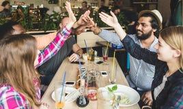 Jeunes attirants de rassemblement dans le caf? Les amis causent, ont l'amusement, cocktails de boissons et mangent images libres de droits