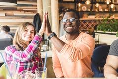 Jeunes attirants de rassemblement dans le caf? Les amis causent, ont l'amusement, cocktails de boissons et mangent photo libre de droits