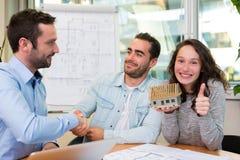 Jeunes attirants rencontrant le vrai agent immobilier au bureau Photographie stock