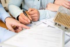 Jeunes attirants rencontrant le vrai agent immobilier au bureau Photographie stock libre de droits