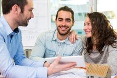 Jeunes attirants rencontrant le vrai agent immobilier au bureau Image libre de droits