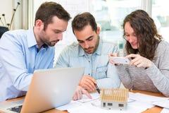 Jeunes attirants rencontrant le vrai agent immobilier au bureau Image stock