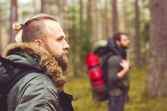 Jeunes augmentant des hommes avec des sacs à dos dans la forêt Photo stock