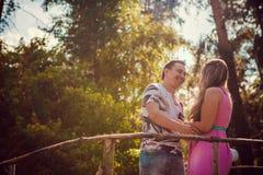 Jeunes baisers et support romantiques de couples au pont sur la forêt d'été de fond Image stock