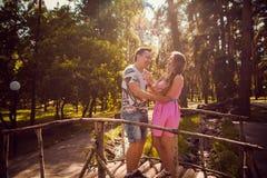 Jeunes baisers et support romantiques de couples au pont sur la forêt d'été de fond Photos stock