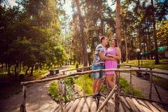 Jeunes baisers et support romantiques de couples au pont sur la forêt d'été de fond Images libres de droits