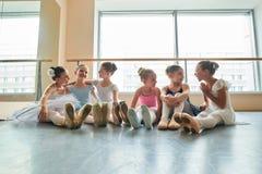 Jeunes ballerines s'asseyant sur le plancher et l'embrassement Photos stock