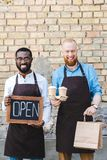 jeunes barman multi-ethniques avec les sacs en papier ouverts de signe et le sourire jetable de tasses de café image stock