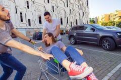 Jeunes beaux amis dupant autour avec un chariot à achats Photographie stock