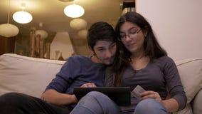 Jeunes beaux couples affectueux faisant des emplettes en ligne ensemble utilisant le PC de comprimé à la maison clips vidéos