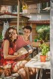 Jeunes beaux couples affectueux heureux se reposant au café en plein air de rue, ayant l'amusement avec l'oreiller Début d'histoi Images stock