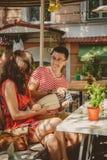 Jeunes beaux couples affectueux heureux se reposant au café en plein air de rue, ayant l'amusement avec l'oreiller Début d'histoi Image libre de droits