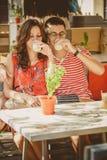 Jeunes beaux couples affectueux heureux se reposant au café en plein air de rue, lait étreignant, boisson yaourt ou Nourriture, c Photos libres de droits