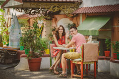 Jeunes beaux couples affectueux heureux se reposant au café en plein air de rue regardant l'appareil-photo Début d'histoire d'amo Photos libres de droits