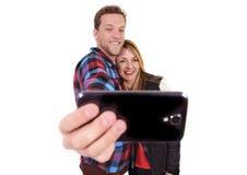 Jeunes beaux couples américains dans l'amour prenant la photo romantique de selfie d'autoportrait ainsi que le téléphone portable Images libres de droits