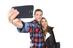 Jeunes beaux couples américains dans l'amour prenant la photo romantique de selfie d'autoportrait ainsi que le téléphone portable Photographie stock libre de droits
