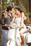 Jeunes beaux couples ayant l'amusement dehors avec le scooter Images libres de droits