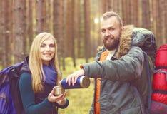 Jeunes beaux couples ayant une coupure dans la forêt et buvant un t Photographie stock
