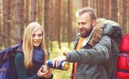 Jeunes beaux couples ayant une coupure dans la forêt et buvant un t Images stock