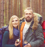Jeunes beaux couples ayant une coupure dans la forêt et buvant un t Image stock