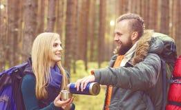 Jeunes beaux couples ayant une coupure dans la forêt et buvant un t Photographie stock libre de droits