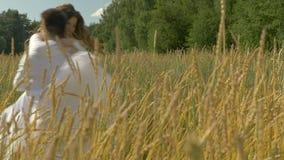 Jeunes beaux couples dans des vêtements blancs étreignant dedans sur un champ de blé banque de vidéos