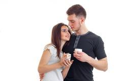 Jeunes beaux couples dans l'amour étreignant et buvant d'un café Photo stock