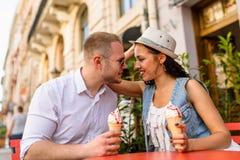 Jeunes beaux couples dans l'amour mangeant la crème glacée  Image stock