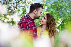 Jeunes beaux couples dans l'amour posant dans le jardin de floraison Images libres de droits
