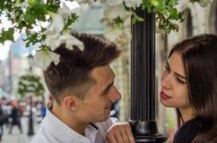 Jeunes beaux couples dans l'amour regardant l'un l'autre dans l'oeil près du courrier avec des fleurs tout en marchant à Lviv en  Images stock