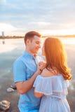 Jeunes beaux couples dans l'amour restant et embrassant sur la plage sur le coucher du soleil Couleurs ensoleillées douces Images stock